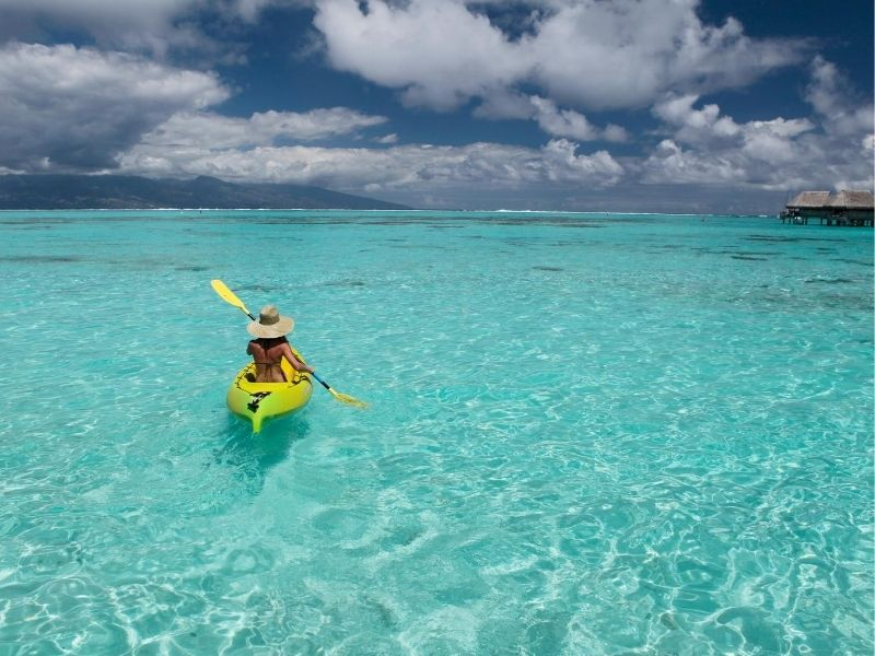 Woman kayaking on clear water, Moorea Island